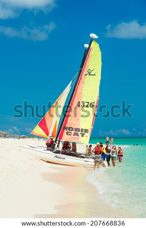 CAYO SANTA MARIA, CUBA - JULY 16, 2014 : Tourists getting ready to sail on a colorful catamaran on a sunny day at the beach - stock photo