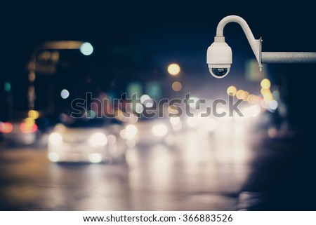 CCTV camera for surveillance driving operating on at night road. Abstract blur bokeh of car dark tones background. - stock photo