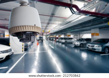 CCTV Camera Operating in car park building - stock photo