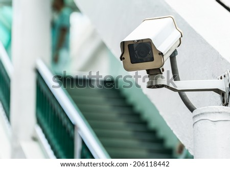 CCTV camera or surveillance operating above stair - stock photo