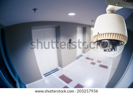 CCTV Camera or surveillance Operating in condominium with fish eye perspective - stock photo