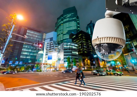 CCTV Camera or surveillance operating on street and building at night - stock photo
