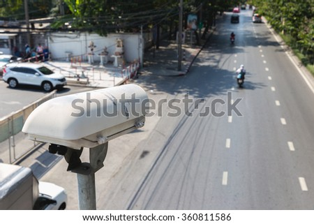 CCTV camera or surveillance operating on traffic road - stock photo