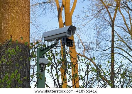 CCTV, Camera Video Surveillance, Security Camera. Camera Surveillance in park. Video Surveillance System. Security CCTV System in the park. - stock photo