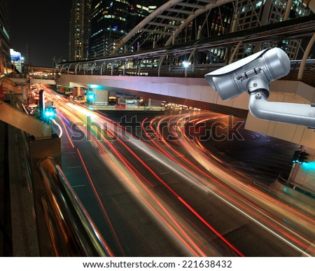 CCTV camera with blurring the night city in background. - stock photo