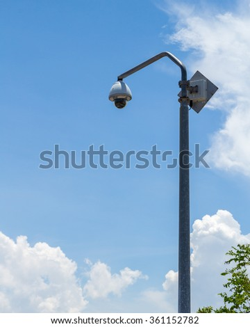 CCTV security camera and surveillance on a pole. - stock photo