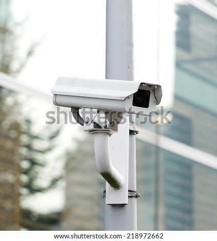 CCTV security camera looking and recording in the city - stock photo