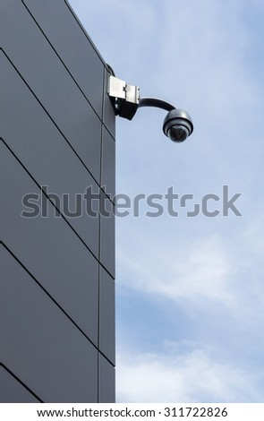 CCTV security camera on facade of building with blue sky in background - vertical image - high angle view - stock photo
