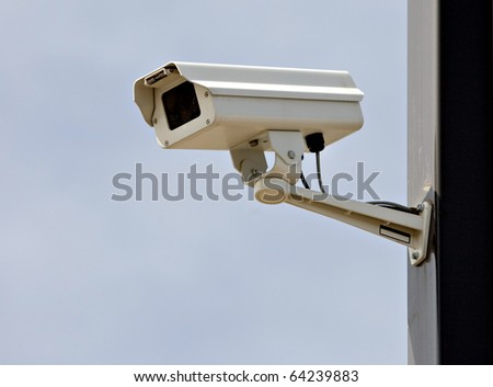 CCTV security camera on pole watching the area - stock photo