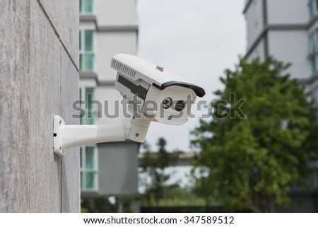 CCTV security camera on stone wall pattern - stock photo