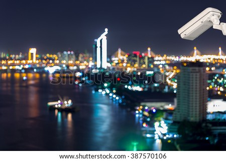 CCTV security on the building. Below is a aerial view of Bangkok city night light at Chao Phaya riverfront and bridge across the river. - stock photo