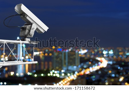 CCTV security on the building. Below is a view of the city lights at night, focus blur. - stock photo