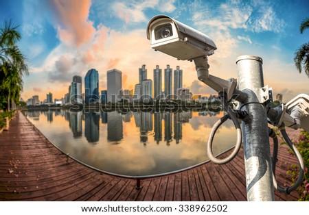 CCTV surveillance camera on top of building - stock photo
