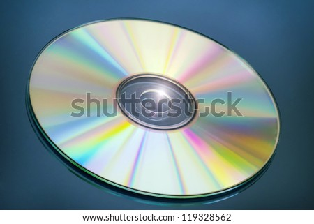 CD with spectrum colors on blue mirror - stock photo