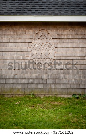 Cedar shingles on the side of a barn with an egg design. - stock photo