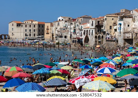 CEFALU, ITALY - AUGUST 21 2016: Cefalu's beach is considered one of the best beaches in Sicily. The beach is a major tourist attraction and is usually crowded during the summer months.