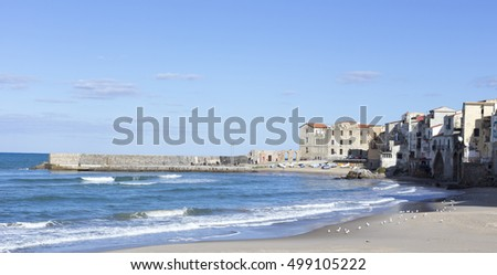 CEFALU, ITALY - JANUARY 02: empty beach of Cefalu leading to its old town in a sunny winter day, Sicily on January 02, 2015