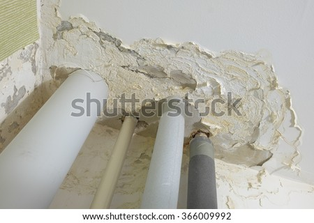 ceiling damage from flooding. the leak on the riser water pipe - stock photo