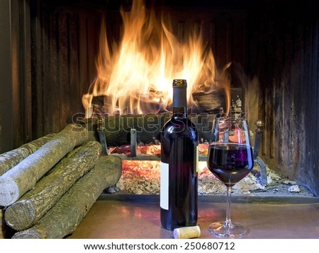 celebrate with a glass of wine, a bottle, in front of a fireplace - stock photo