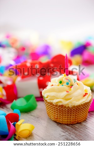 Celebrating a special day. Side view image of a cupcake with multicolored confetti as a frame and a gift box with red ribbon on the background - stock photo