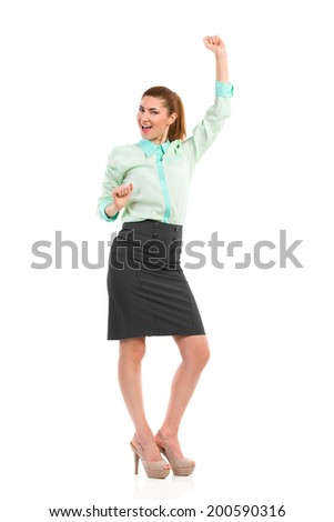 Celebrating businesswoman. Smiling attractive woman is dancing with arms raised. Full length studio shot isolated on white. - stock photo