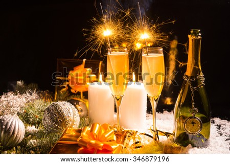 Celebrating Christmas and the New Year festive season with sparklers and champagne in a still life arrangement with burning candles gifts and decorations