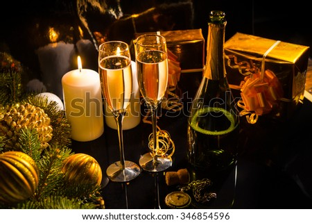 Celebrating Christmas Eve with glasses and a bottle of champagne, burning candles, gold gifts and Xmas decorations in warm lighting at night