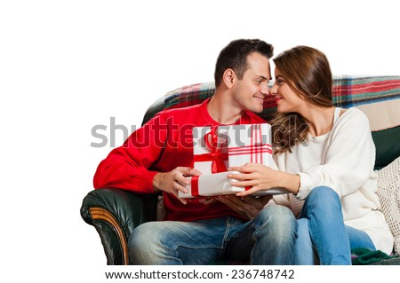 Celebrating Christmas together. Beautiful young couple sitting on the couch and smiling at camera exchanging gifts isolated over white background - stock photo