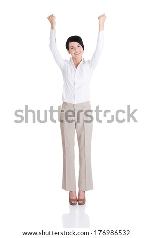 Celebrating happy young businesswoman in full length with her arms up. Success / winner business woman. - stock photo