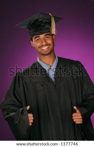 celebrating his achievement this educated graduate puts his thumbs up - stock photo