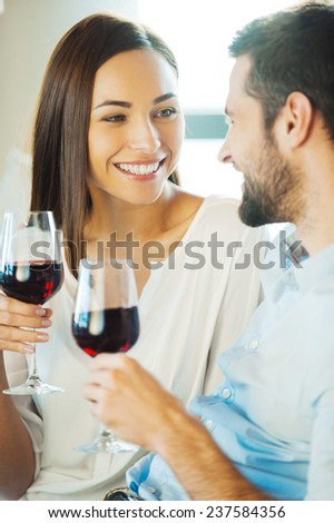 Celebrating love. Beautiful young loving couple sitting close to each other and drinking red wine - stock photo