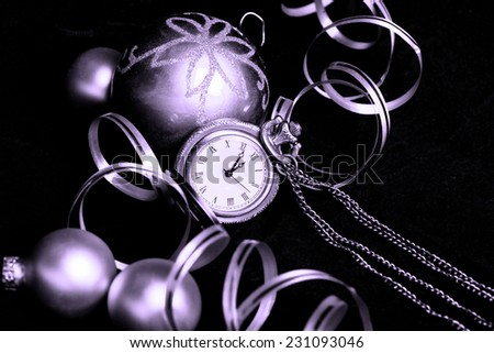 Celebrating New Years concept with vintage watch, baubles and decoration ribbon on black (purple toning) - stock photo