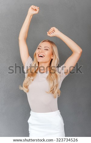 Celebrating success. Excited young blond hair woman keeping arms raised and keeping eyes closed while standing against grey background - stock photo