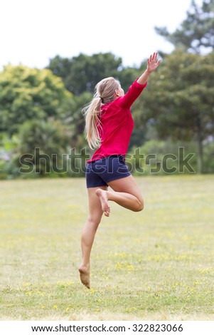 celebrating success outdoors concept - dynamic beautiful young woman in shorts jumping with arms raised for fun and happiness in city park,natural summer daylight,view from the back