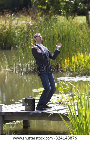 celebrating success outdoors concept - thrilled modern businessman applauding himself with euphoria for  corporate achievement on bridge near water,natural summer daylight - stock photo
