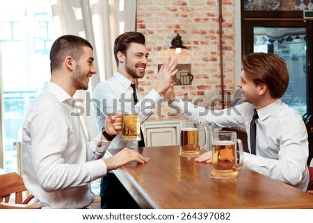 Celebrating success together. Two cheerful young men in shirt and tie gesturing while drinking beer at the bar counter - stock photo