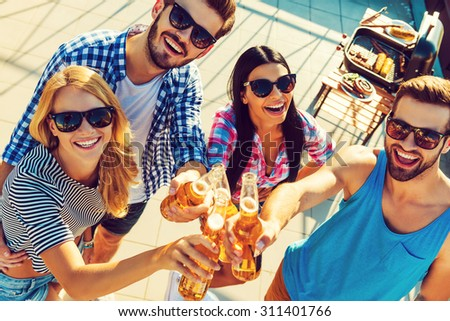 Celebrating their friendship. Top view of four cheerful young people clinking glasses with beer and looking at camera while standing outdoors - stock photo