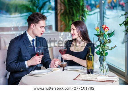 Celebrating wedding anniversary together in a restaurant. Romantic dinner in the restaurant. Young loving couple visits a restaurant and raised their glasses of wine and looking at each other - stock photo
