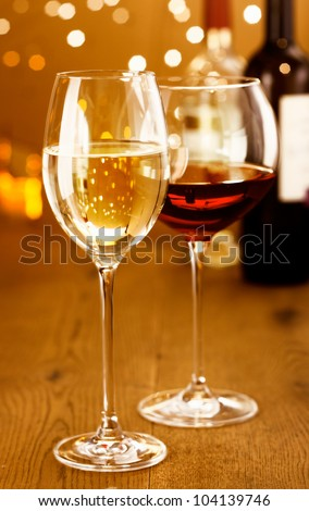 Celebrating with glasses of red and white wine against a sparkling bokeh of festive party lights - stock photo