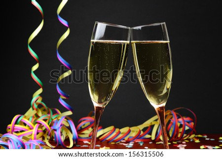 Celebrating with sparkling wine and colorful paper streamers, black background. - stock photo