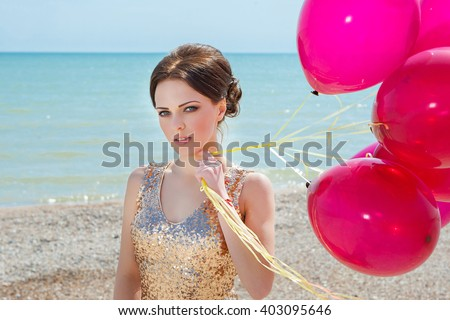 celebration and lifestyle concept - beautiful woman in gold dress with red balloons on the sea