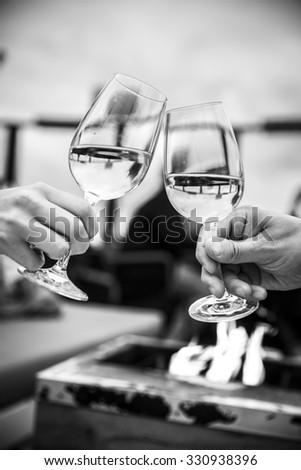 Celebration. black and white shot of people holding glasses of white wine making a toast - stock photo