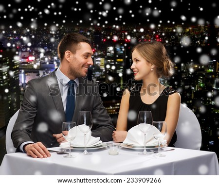 celebration, christmas, holidays and people concept - smiling couple at restaurant over snowy night city background