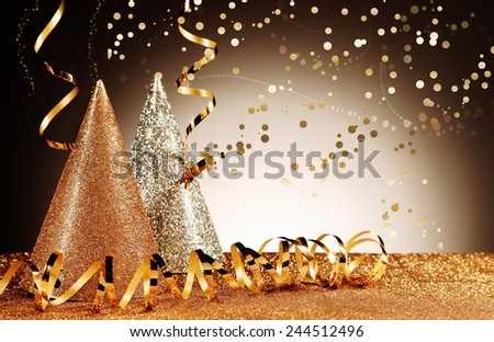 Celebration Concept - Close up Glittery Party Cone Hats with Shiny Streamers with Confetti Effect on Glittery Table in Front Gradient Brown Background. - stock photo