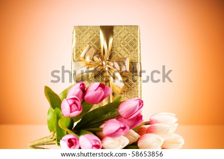 Celebration concept - gift box and tulip flowers - stock photo