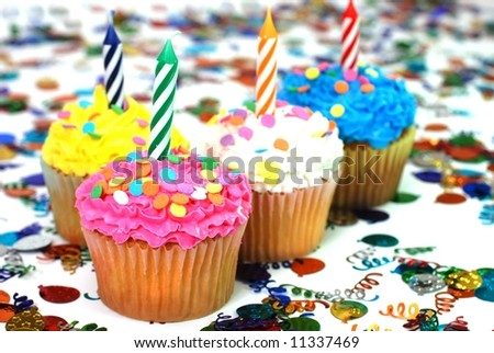 Celebration cupcakes with candles and sprinkles.  Confetti in background.