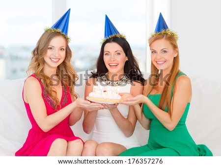 celebration, food, friends, bachelorette party, birthday concept - three smiling women wearing blue hats holding cake with candles - stock photo
