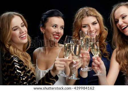 celebration, friends, bachelorette party and holidays concept - happy women clinking champagne glasses over black background