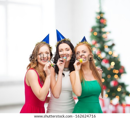 celebration, friends, bachelorette party, birthday concept - three smiling women wearing blue hats and blowing favor horns - stock photo