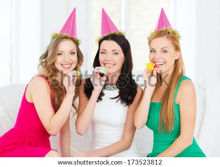 celebration, friends, bachelorette party, birthday concept - three smiling women wearing pink hats and blowing favor horns